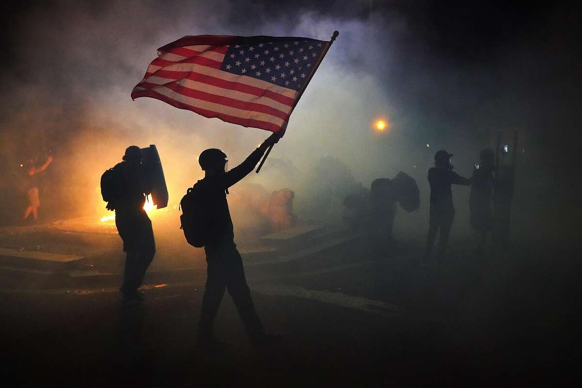 PORTLAND, OR - JULY 21: A protester flies an American flag while walking through tear gas fired by federal officers during a protest in front of the Mark O. Hatfield U.S. Courthouse on July 21, 2020 in Portland, Ore. The federal police response to the ongoing protests against racial inequality has been criticized by city and state elected officials. (Photo by Nathan Howard/Getty Images) *** BESTPIX ***