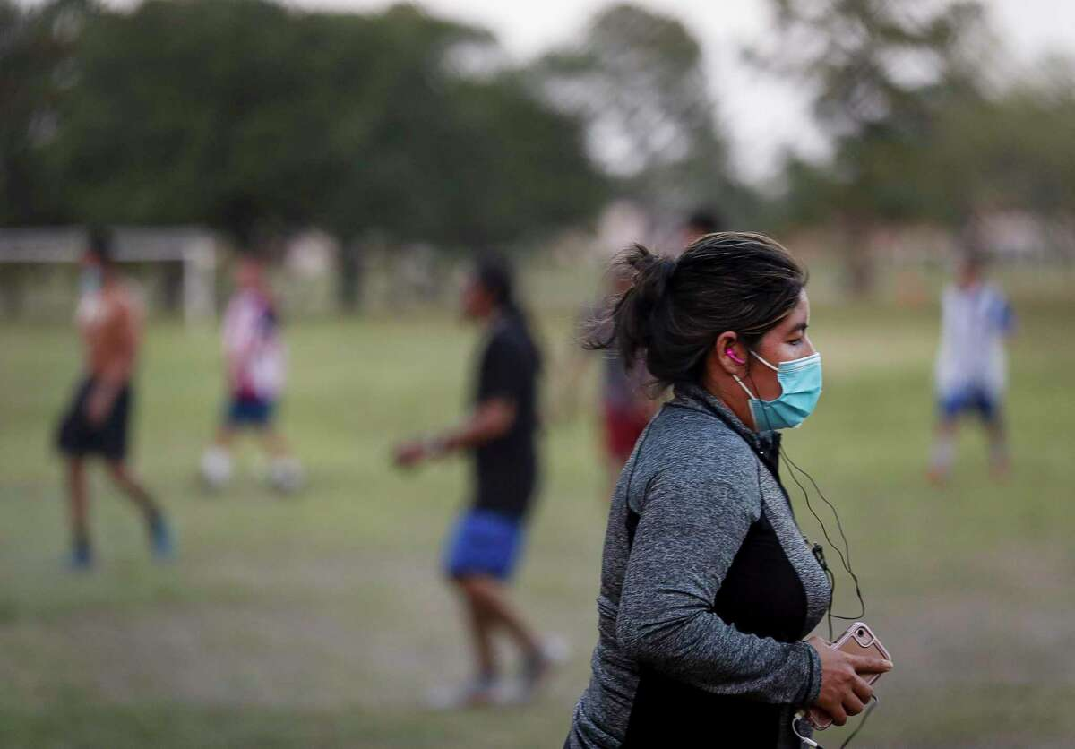 A woman wears a face mask while exercising at Burnett Bayland Park on Thursday, July 16, 2020, in Houston. The coronavirus is raging through Hispanic communities in the Houston area, and two of the five ZIP codes with the highest positivity rates are in Gulfton and Sharpstown neighborhoods.