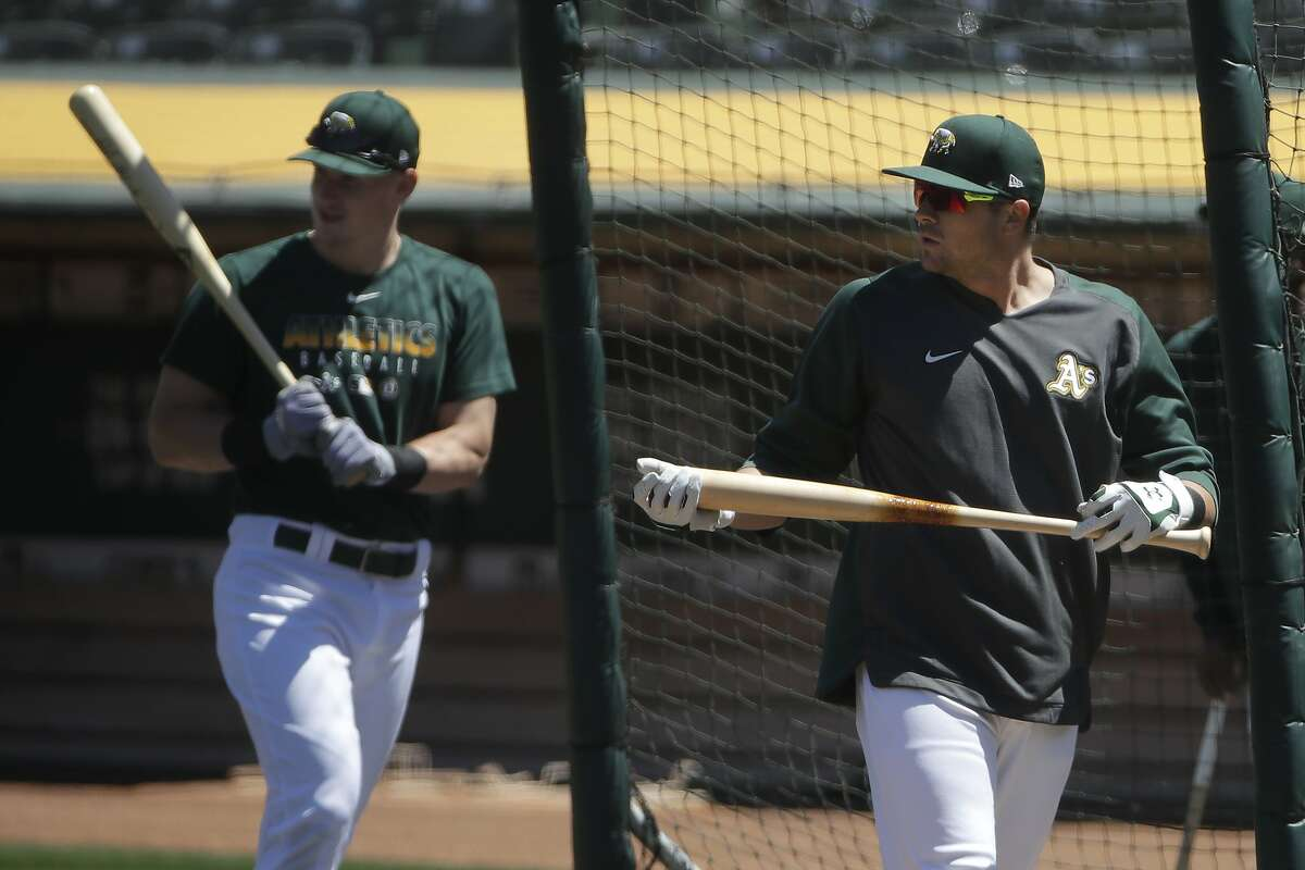 Oakland Athletics' Austin Allen, right, and Sean Murphy stand in the batting cage during a baseball practice in Oakland, Calif., Saturday, July 4, 2020. (AP Photo/Jeff Chiu)