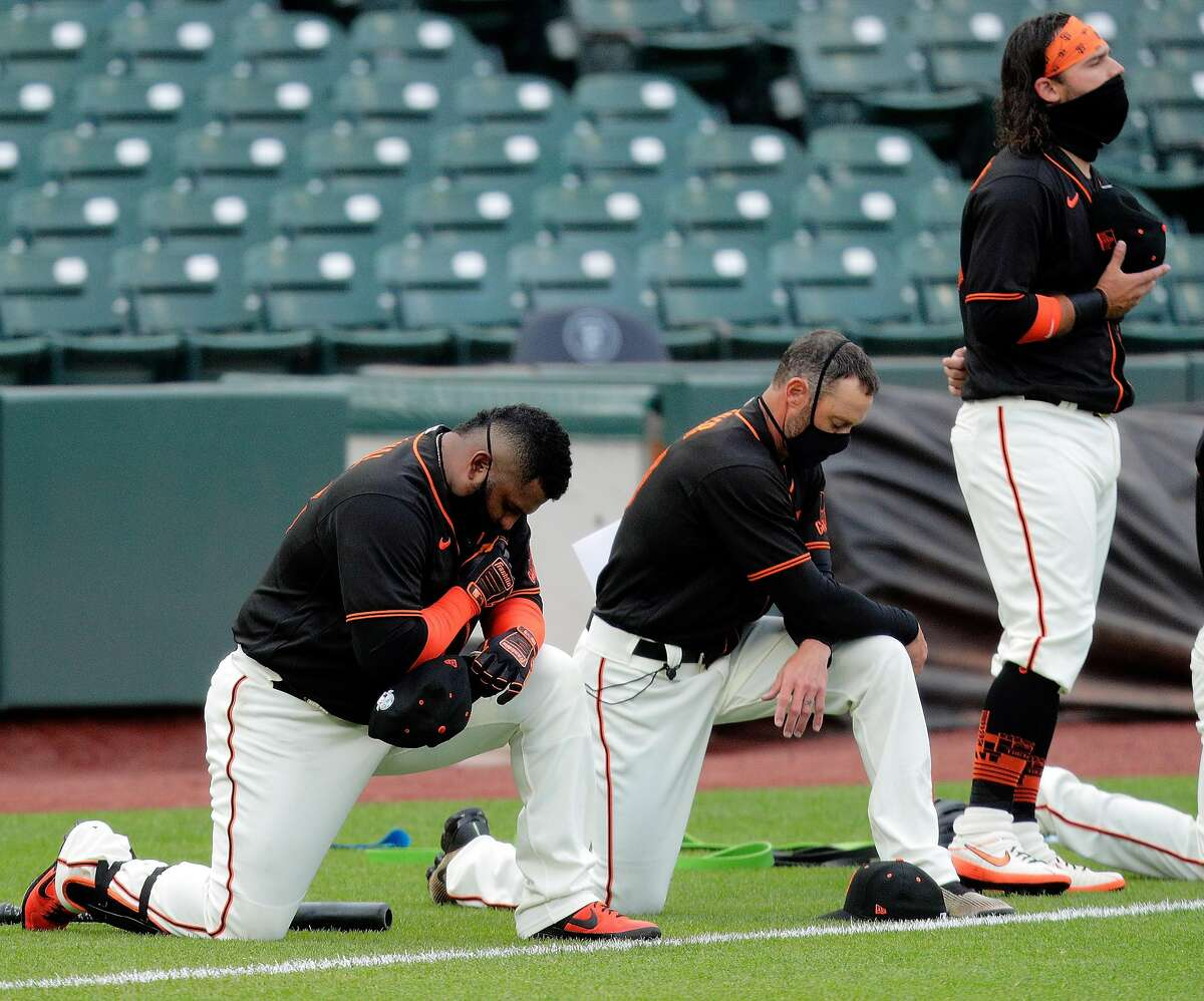 Giants manager Gabe Kapler, center, and Pablo Sandoval, left, take a knee during the National Anthem with Brandon Crawford, right before the San Francisco Giants played the Oakland Athletics in a summer exhibition game at Oracle Park in San Francisco, Calif., on Tuesday, July 21, 2020.