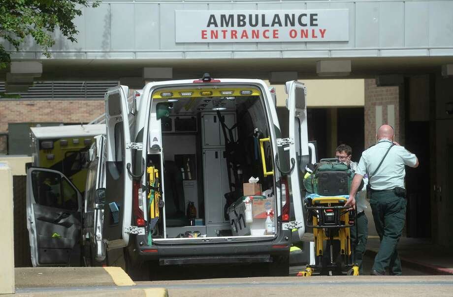 Ambulances are parked in the Emergency Room drive at Christus St. Elizabeth Hospital in Beaumont Tuesday, where crews clean and wait after making patient deliveries.