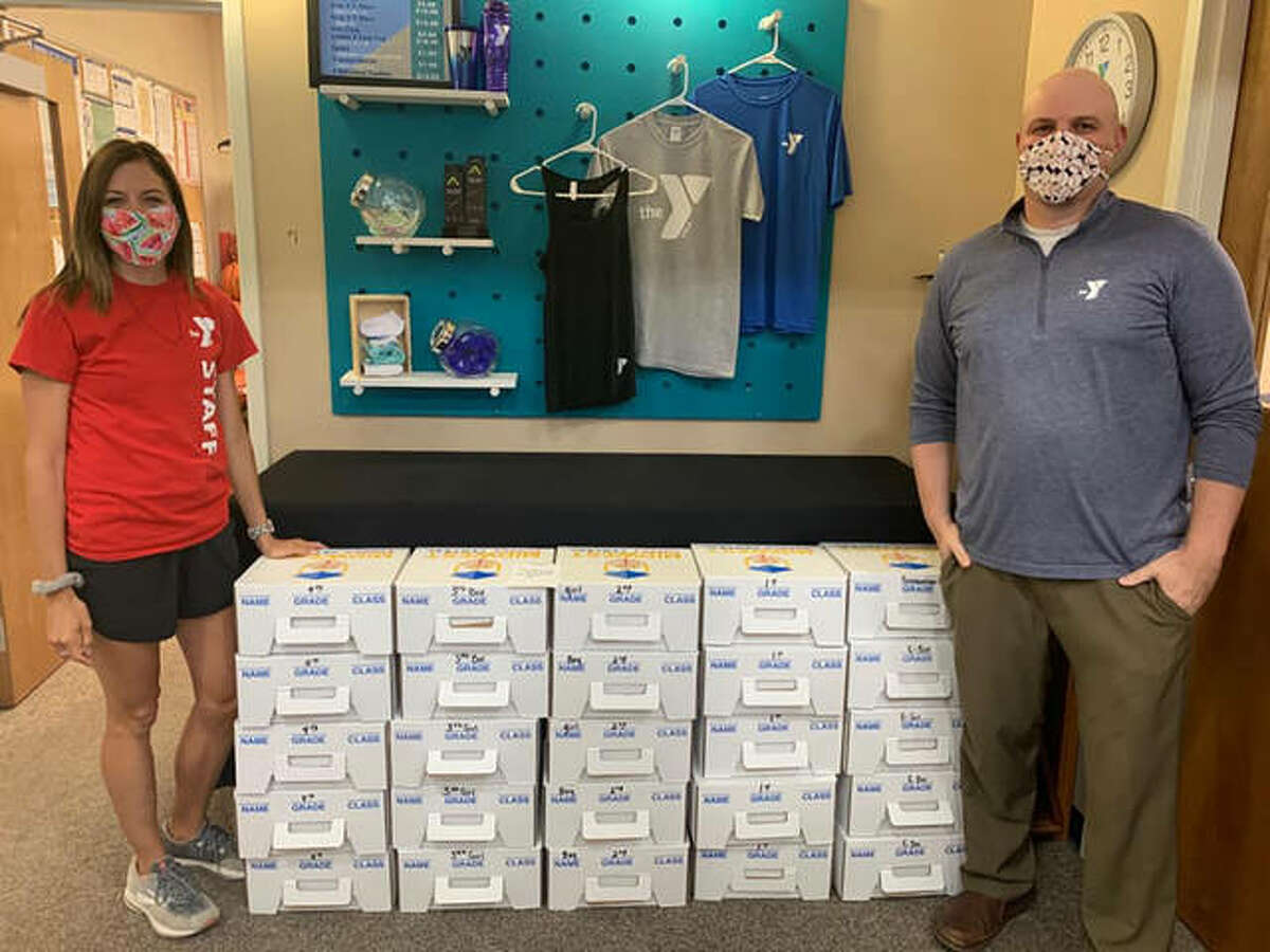 Emily Reuschel (left), Mount Sterling Community Center YMCA's senior program director, and branch Executive Director Jeff Summers display 25 school supply kits the YMCA has available for families in the community.