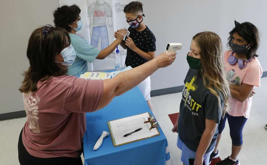 Amid concerns of the spread of COVID-19, science teachers Ann Darby, left, and Rosa Herrera check-in students before a summer STEM camp at Wylie High School Tuesday, July 14, 2020, in Wylie, Texas. Photo: LM Otero/AP / Copyright 2020 The Associated Press. All rights reserved.