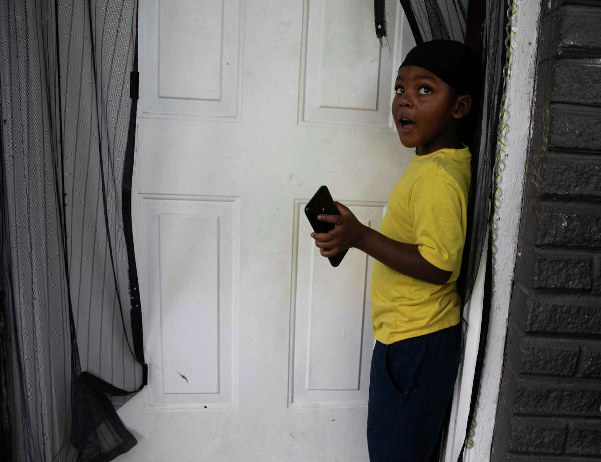 Caleb Tillis, 4, hangs by the door of a one-bedroom apartment where he lives with his parents, Sharetta Burleson and Anthony Tillis, Tuesday, July 21, 2020, in Houston. The family aren't the only ones in their two-story apartment complex who face eviction.