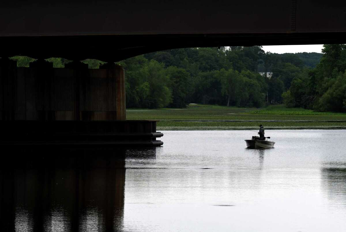 An angler tries his luck under the Route 9 bridge while fishing on the Mohawk River on Wednesday, July 22, 2020, in Halfmoon, N.Y. (Will Waldron/Times Union)