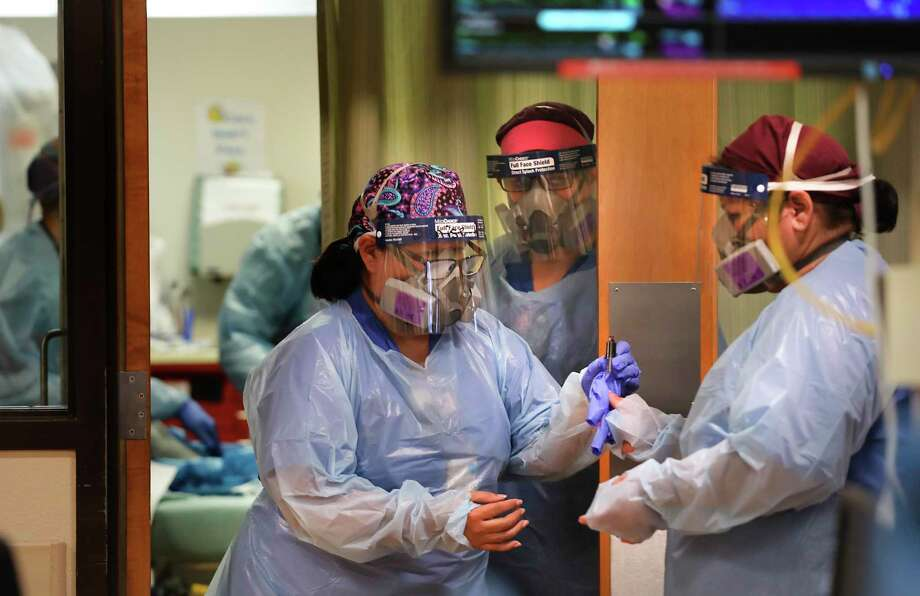 A nurse passes a blood sample of a COVID-19 patient to another nurse for testing in the ER at Christus Santa Rosa Hospital in the Medical Center, on Monday, July, 20, 2020. Photo: Bob Owen / San Antonio Express-News / ©2020 San Antonio Express-News