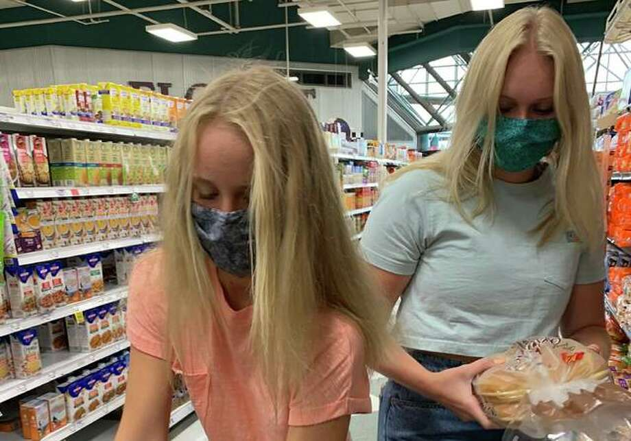 Lily Freer, left, 13, and her sister, Taylor, 16, shop for this year's Christmas in July. This year's event will follow COVID-19 social distancing guidelines with sloppy Joes available for pick up 10:30 a.m. to 1:30 p.m. Friday, July 31, at Freer Auto Body in Godfrey. Along with sandwiches, supporters will also get a bag of chips and a drink. All proceeds go toward Community Christmas sponsored by the United Way and The Telegraph.
