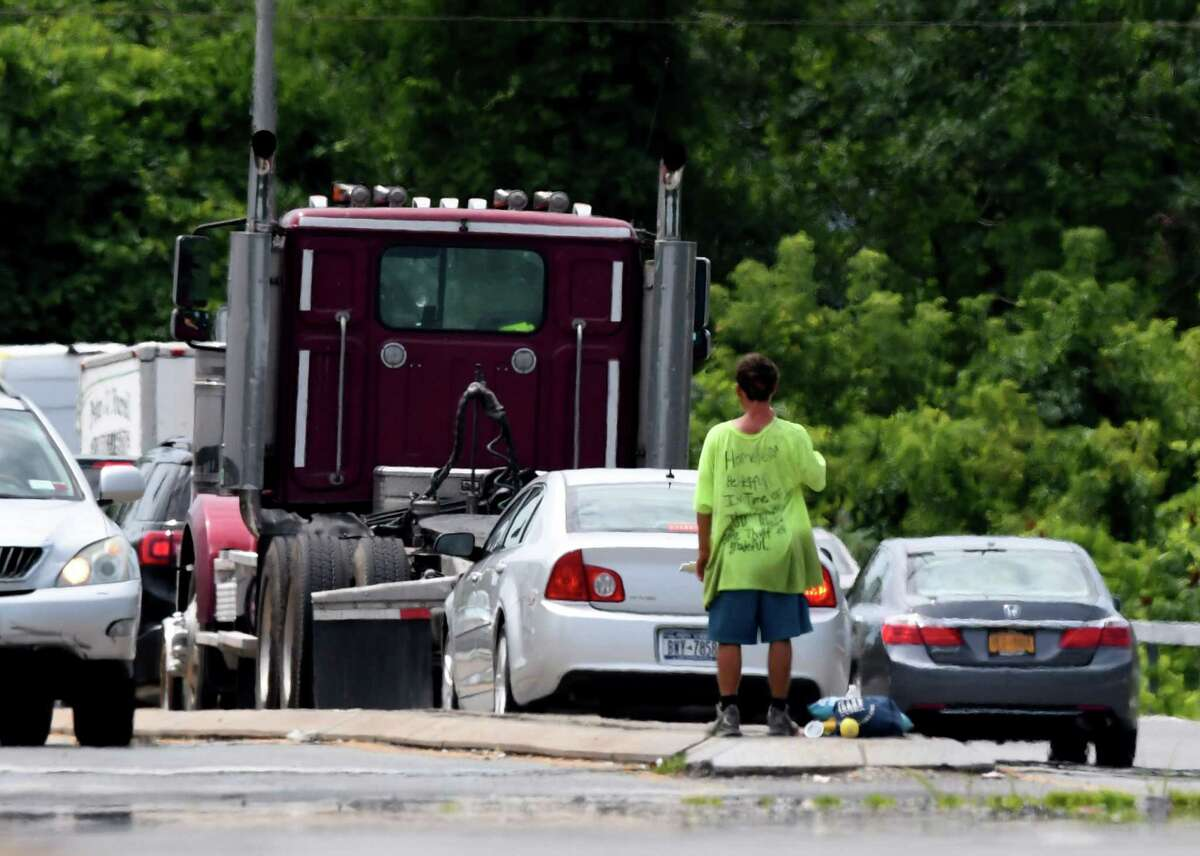 A panhandler works the traffic lights at Everett Road Extension on the Albany-Colonie border at I-90 on Wednesday, July 22, 2020, in Albany, N.Y. Colonie just across the border is proposing a new local law which will make it a violation to solicit money or other things of value from motorists stopped in traffic or at traffic control devices. (Will Waldron/Times Union)