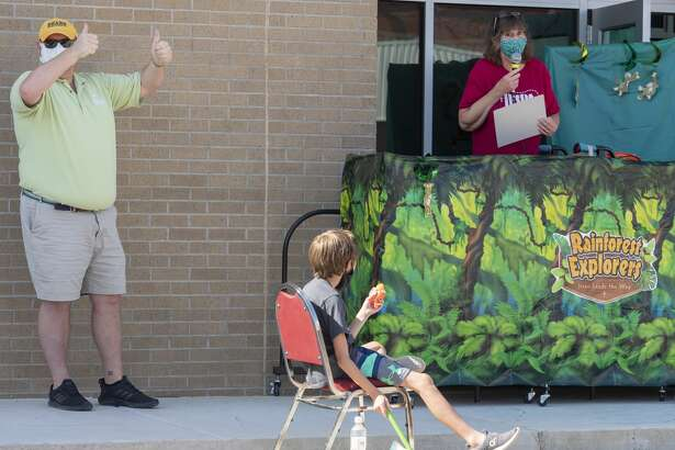 Craig Stoker, with West Texas Food Bank, accepts a donation of $2000 from Jane Pase, VBS director, 07/22/2020 morning during Grace Lutheran Church Vacation Bible School. Church members collected the donations to help aid area families. Tim Fischer/Reporter-Telegram