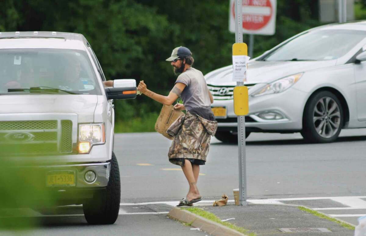 A driver gives money to a man as he panhandles at the Walmart entrance on Washington Ave. Extension on Wednesday, July 22, 2020, in Albany, N.Y. The neighboring town of Colonie is proposing a new local law which will make it a violation to solicit money or other things of value from motorists stopped in traffic or at traffic control devices. (Paul Buckowski/Times Union)