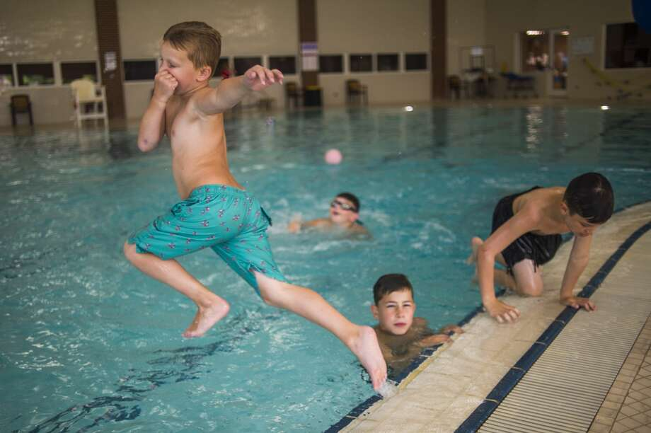 Parker Koch, 7, jumps into the pool during a day camp Wednesday, July 22, 2020 at Greater Midland Community Center. (Katy Kildee/kkildee@mdn.net) Photo: (Katy Kildee/kkildee@mdn.net)