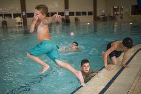 Parker Koch, 7, jumps into the pool during a day camp Wednesday, July 22, 2020 at Greater Midland Community Center. (Katy Kildee/kkildee@mdn.net)