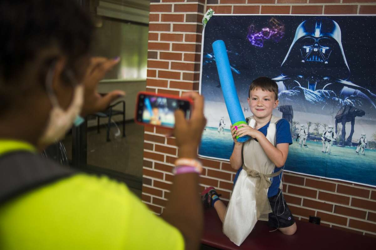 Aiden Vuczek, 7, poses for a photo with his handmade lightsaber and Jedi robes during Star Wars day camp Wednesday, July 22, 2020 at Greater Midland Community Center. (Katy Kildee/kkildee@mdn.net)
