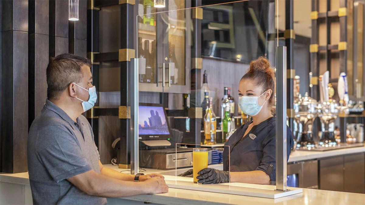 Masked guest and server at a bar in the Hyatt Regency Jacksonville.