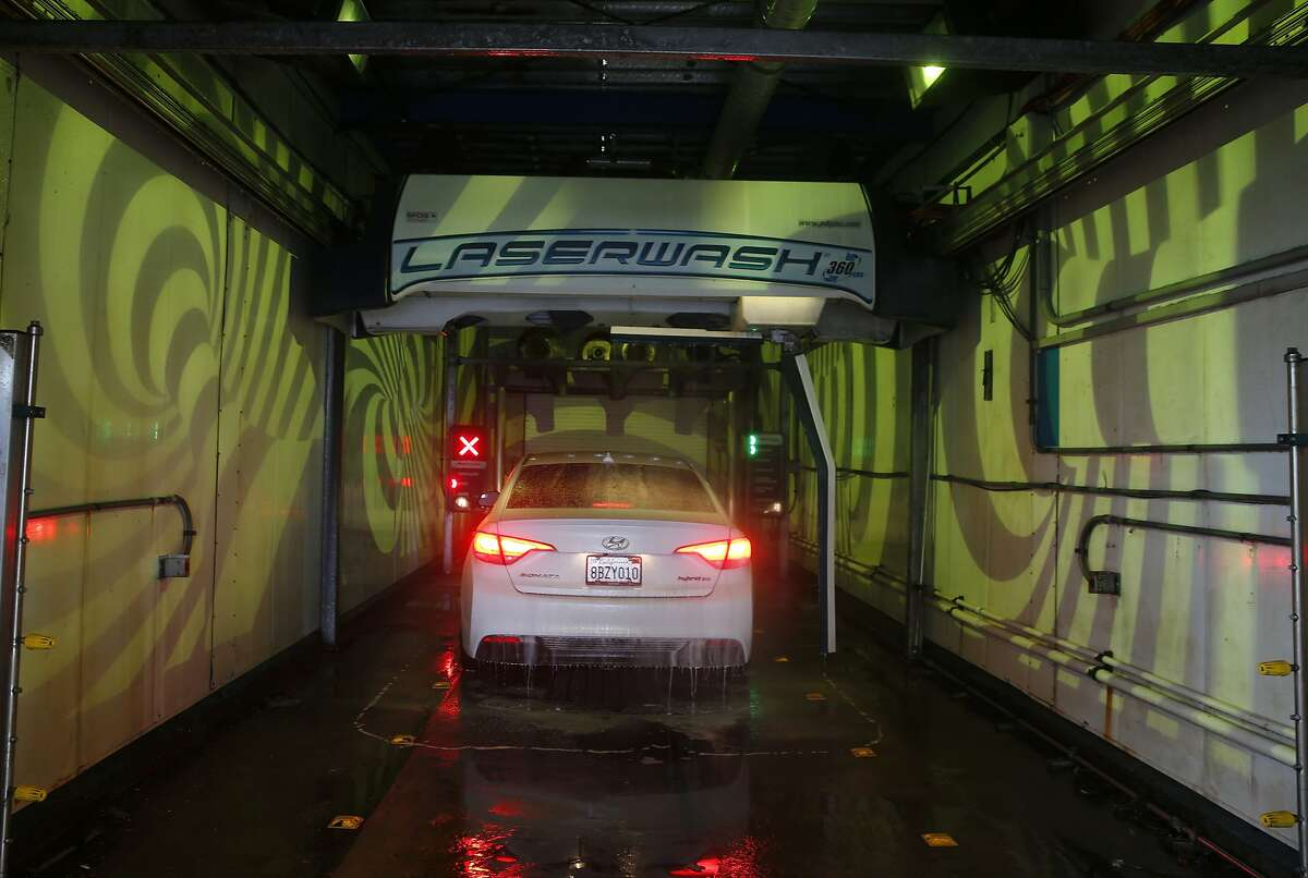 A driver is entertained by a colorful virtual reality light display while his car is washed in San Bruno, Calif. on Wednesday, July 15, 2020. The Shell gas station and car wash across from the Tanforan shopping mall is also adorned with nautically-themed and satirical sculptures.