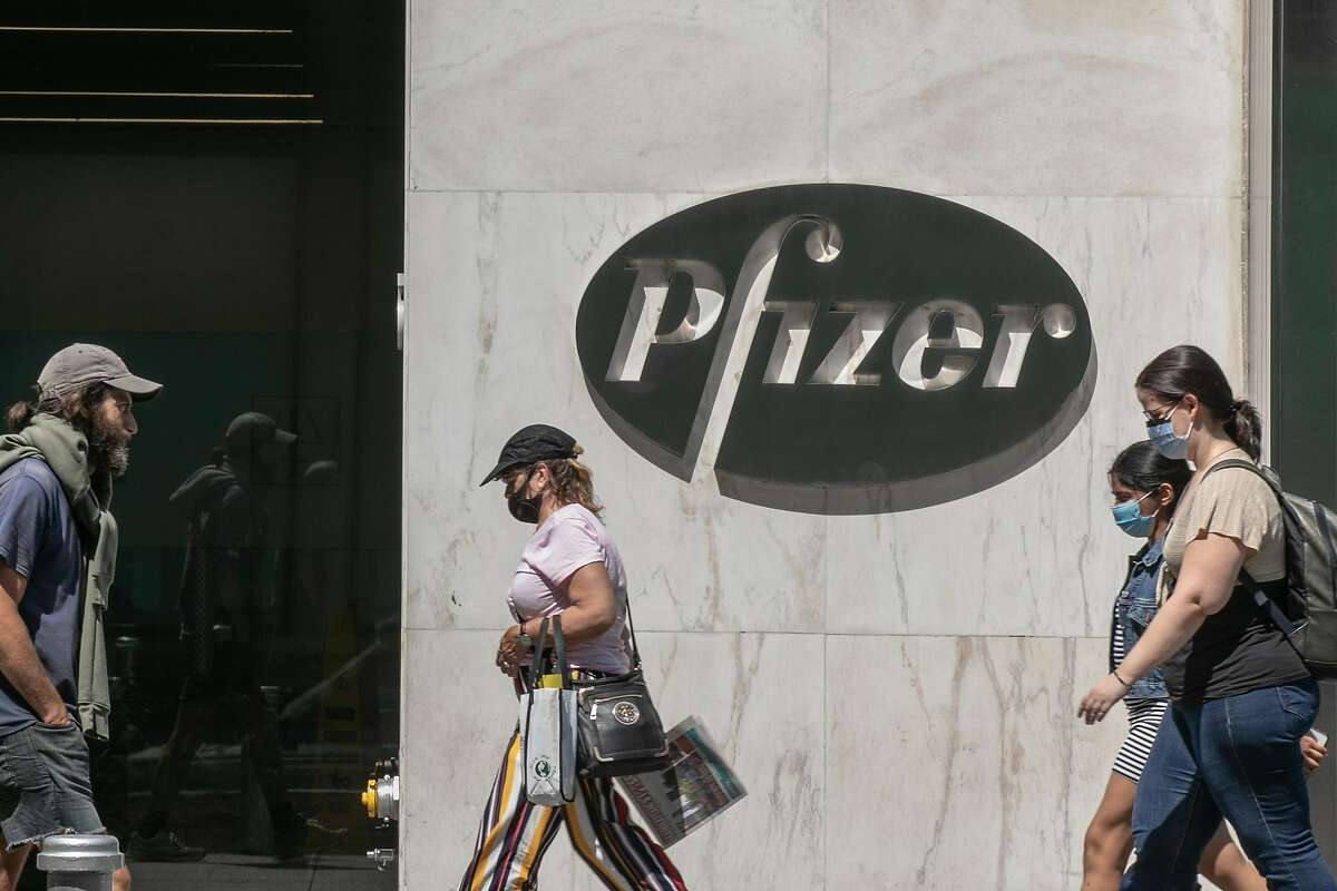 FILE - Pedestrians wearing protective masks walk past Pfizer Inc. headquarters on July 22, 2020 in New York City. Pfizer and German biotechnology firm BioNTech have agreed to supply the U.S. government with 100 million doses of coronavirus vaccine under a $1.95 billion deal.