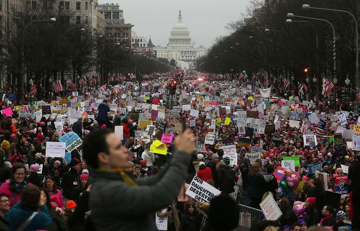 WASHINGTON, DC - JANUARY 21: Protesters walk during the Women's March on Washington, with the U.S. Capitol in the background, on January 21, 2017 in Washington, DC. Large crowds are attending the anti-Trump rally a day after U.S. President Donald Trump was sworn in as the 45th U.S. president. (Photo by Mario Tama/Getty Images)