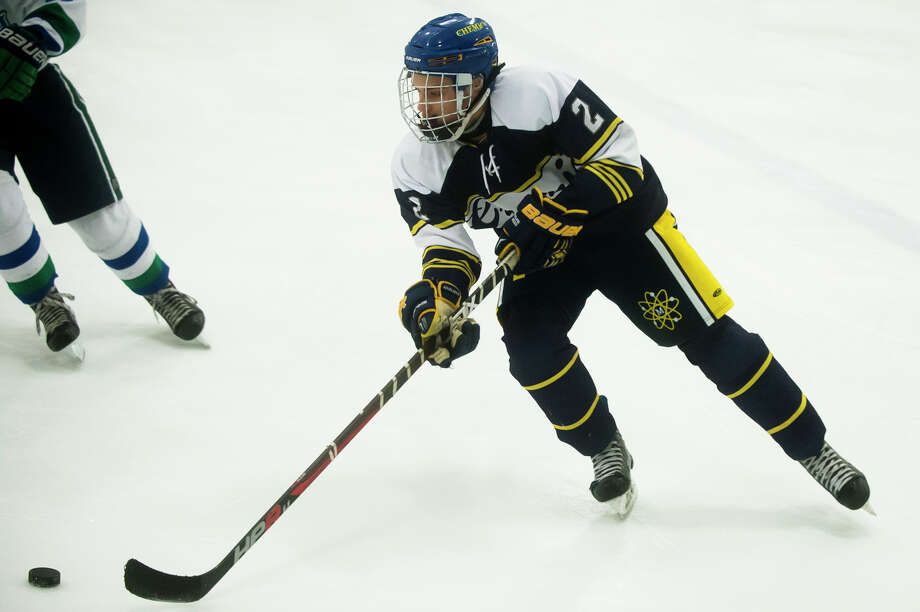 Midland High's Matthew Babinski carries the puck during a Feb. 14, 2018 game against Saginaw Heritage. Photo: Daily News File Photo