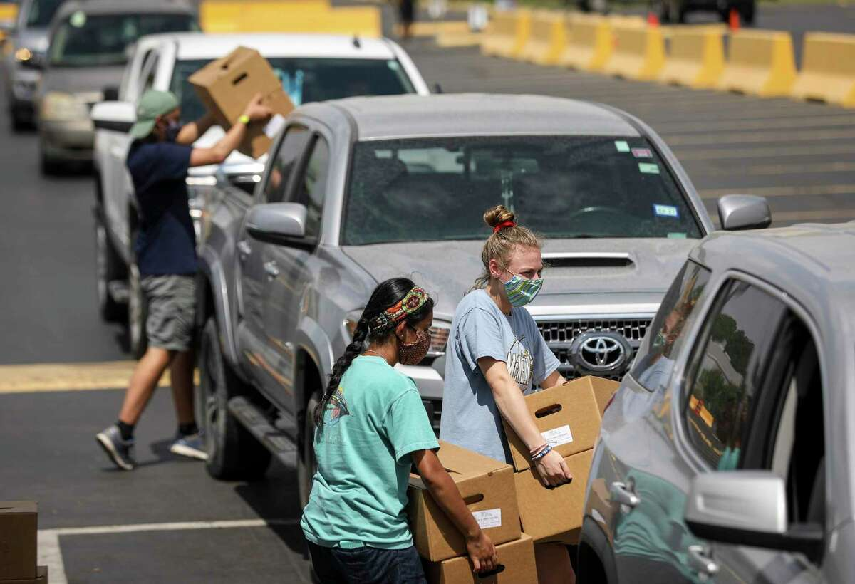 """Paige Daniels, 17, right, and Neha Shaw, 17, center, load boxes of food into a trunk during a food distribution at Imagen Venues in Houston. """"I honestly just like to give up my time to others,"""" Daniels said."""