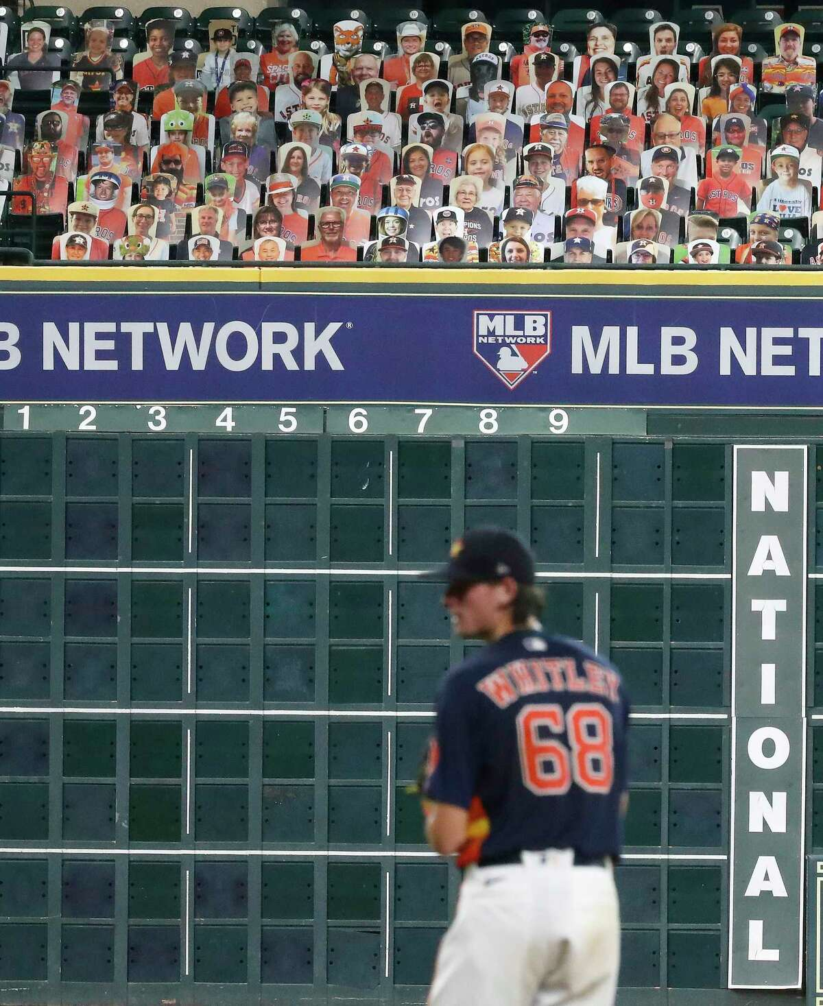 Houston Astros pitcher Forrest Whitley pitches with cardboard cutouts of fans in the Crawford Boxes behind him during an intrasquad game during the Astros summer camp at Minute Maid Park, Wednesday, July 22, 2020, in Houston.