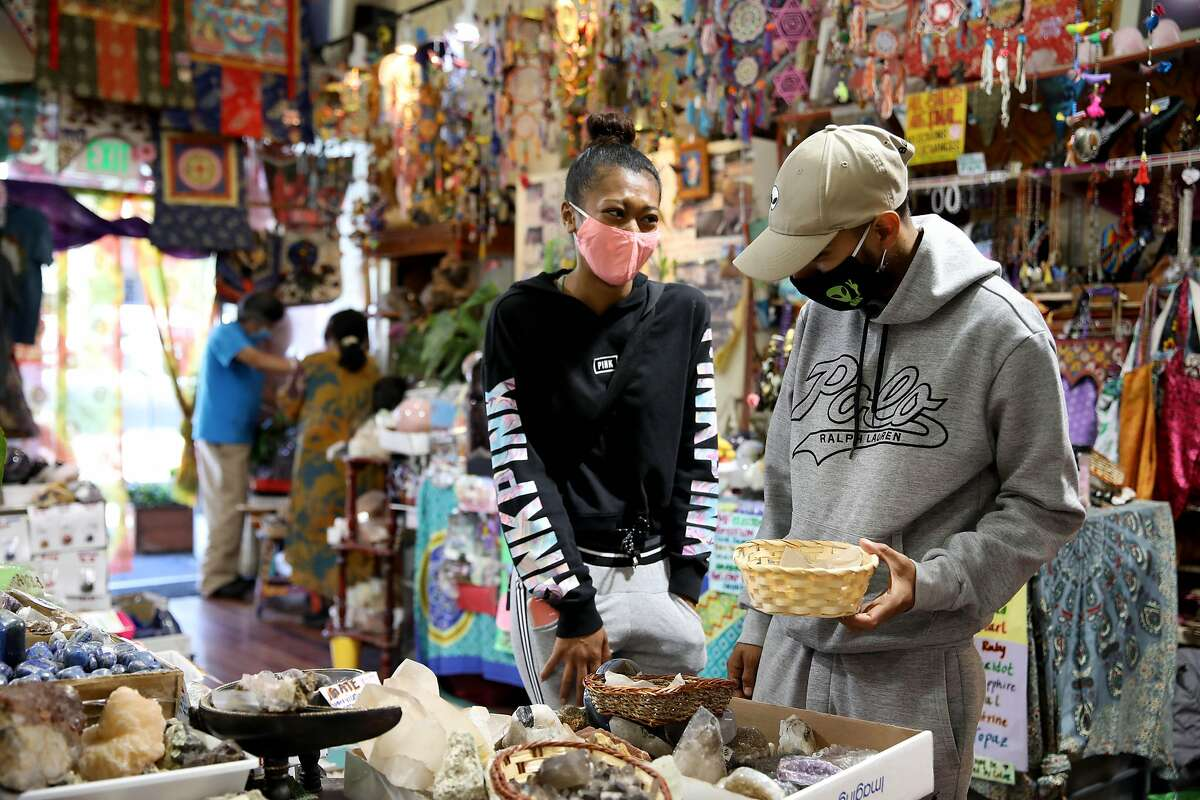 """Kayla Scott and Edgar Unzueta, owners of Vegan Alien, shop inside Nongnooch """"Noot"""" Suwannajan's clothing and crystal shop, The Love of Ganesha, located at 1573 Haight St., on Wednesday, July 22, 2020, in San Francisco, Calif. The shop's been opened since April 11, 1999. Californians can't do anything fun indoors these days, especially if they're in a watchlist county. There's one exception: indoor shops that are not in malls are still open and The Love of Ganesha is one of those places."""