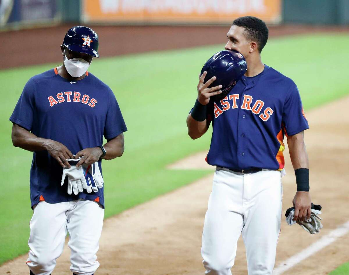Houston Astros outfielder Michael Brantley covers his face with his batting helmet as he talked with third base coach Gary Pettis during an intrasquad game during the Astros summer camp at Minute Maid Park, Wednesday, July 22, 2020, in Houston.