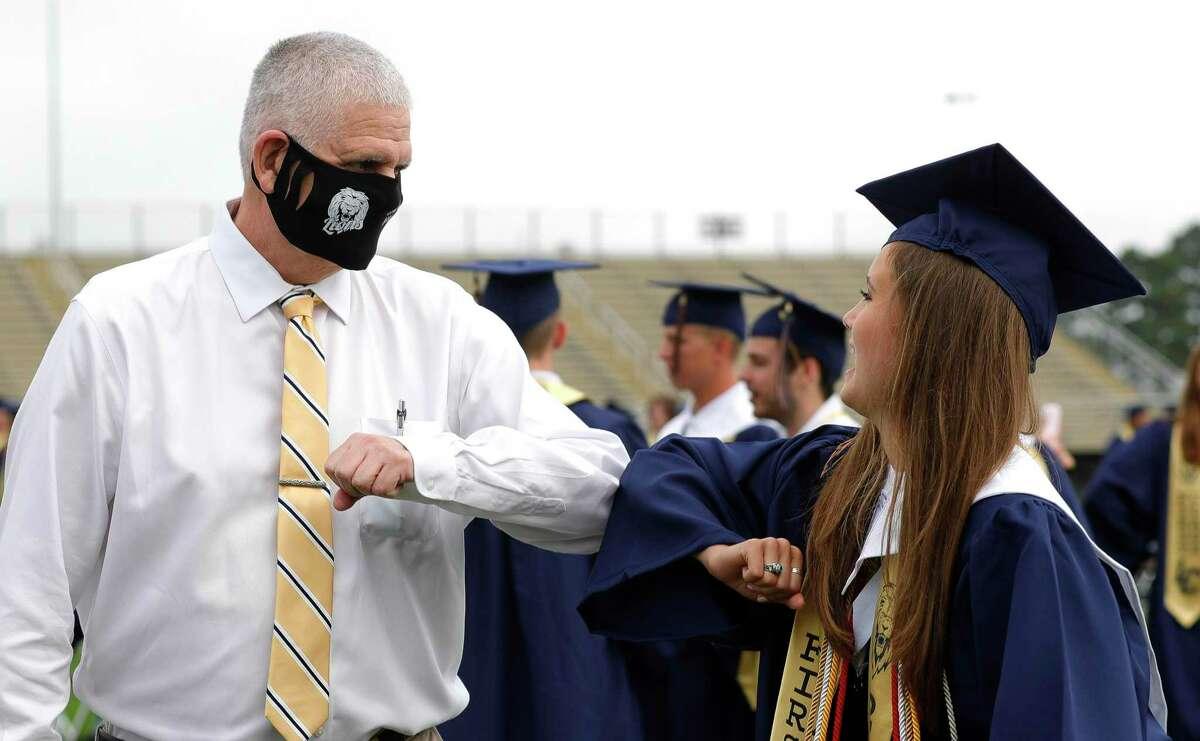 Lake Creek Principal Phil Eaton, left, elbow bumps Abby Kelly before a graduation ceremony at MISD Stadium, Thursday, June 4, 2020, in Montgomery. Eaton contracted and surived COVID-19 after a 51-day battle with the virus. The 220 students in the school's inaugural graduating class attended the outdoor ceremony with social distancing and other safety guidelines.