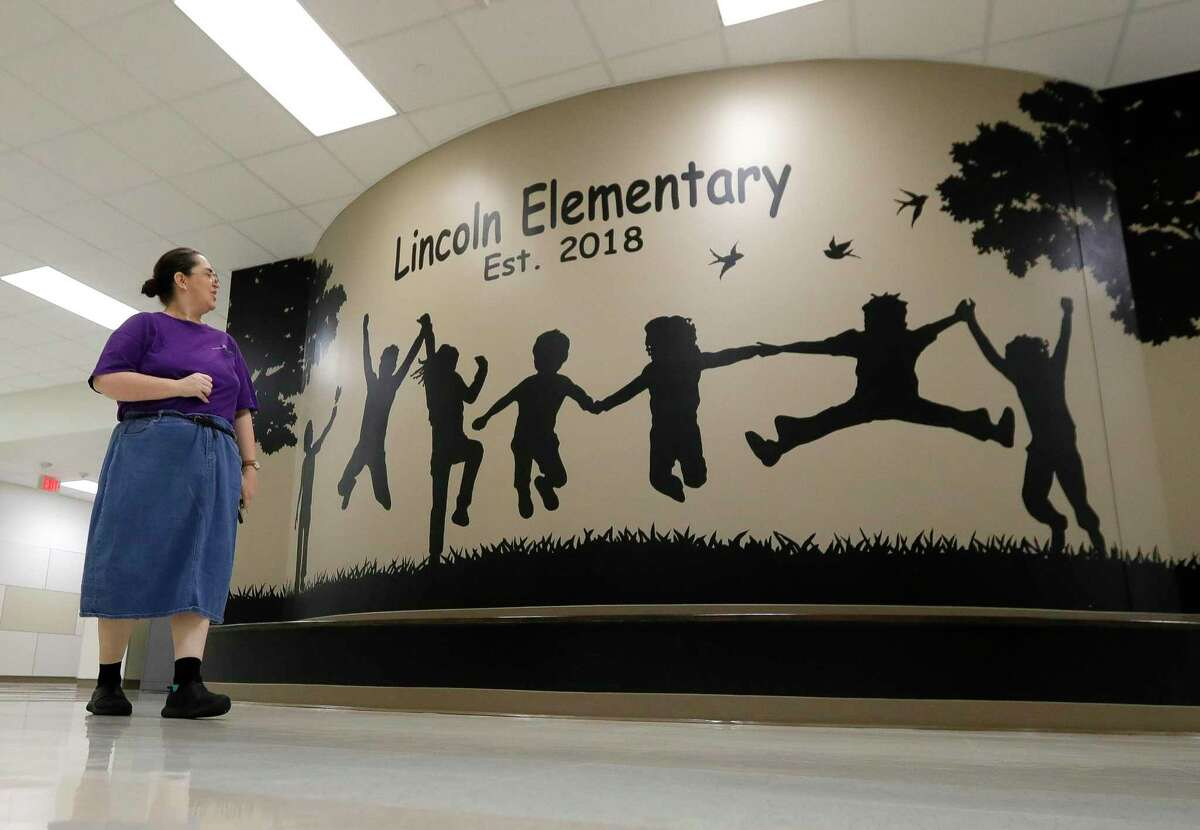 Custodian Joann Davis walks past a mural at Lincoln Elementary School, Thursday, March 12, 2020, in Montgomery. Members of Montgomery ISD's service for education management began additional disinfectant steps at all of the district's 10 schools. Superintendent Beau Rees announced the district would close two days ahead of spring break in an abundance of caution after health officials announced Montgomery County's first 'presumptive positive' case of the coronavirus on March 11.