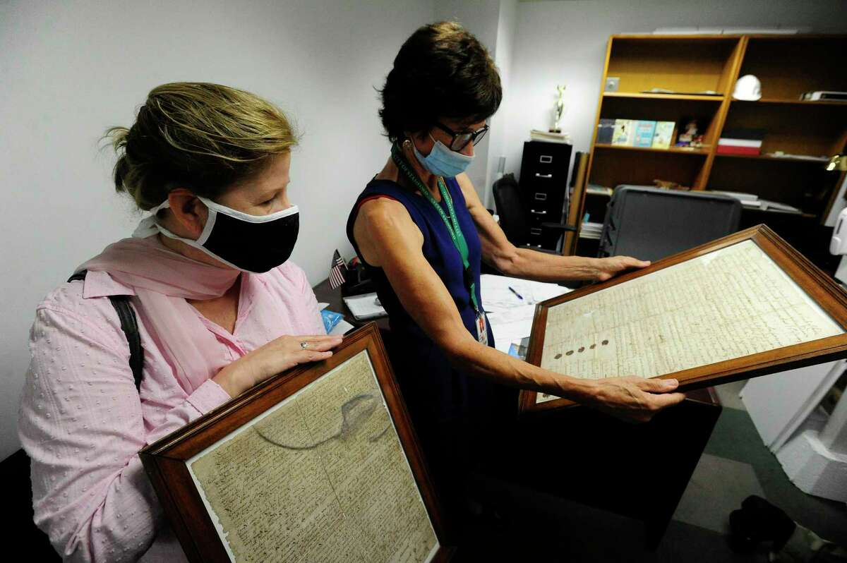 From left, Alice Knapp, President of Ferguson Library and Lyda Ruijter, Stamford Town Clerk, look at the original deed of the city on July 17, 2020 at the Government Center in Stamford, Connecticut. The deed and other records from that time period are being sent for restoration and preservation by Northeast Document Conservation Center in Andover, Massachusetts.