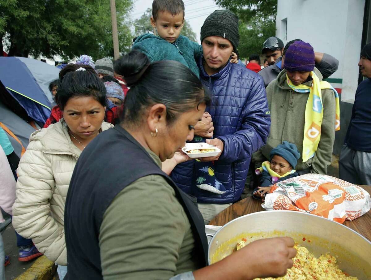 Jose Pineda, center, from Honduras, carries his 3-year-old son Luis Jose as they receive breakfast at the asylum refugee camp in Matamoros, MX. The meal was being served by religious volunteers that was paid for by Team Brownsville.