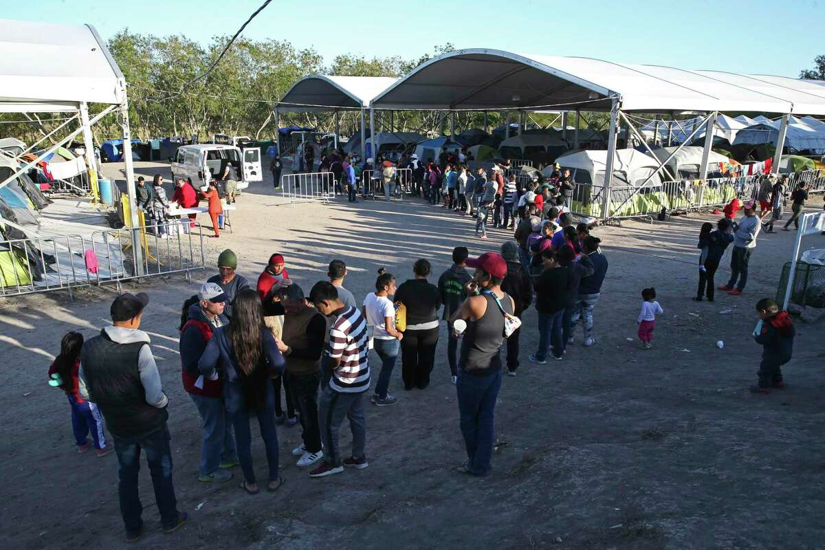 A line forms as Iglesia Puerta del Cielo hands out sweet bread and coffee at a migrant camp by the Gateway International Bridge in Matamoros, Mexico, Thursday, Feb. 6, 2020. The camp started after the U.S. implemented the Migrant Protection Program also known as the Return to Mexico plan. Migrants awaiting their asylum-seeking court date started camping by the sidewalk leading to the bridge. It was recently moved away from the sidewalk on land that was used as soccer fields by the Rio Grande. Currently, the camp is housing around 2,200 migrants.