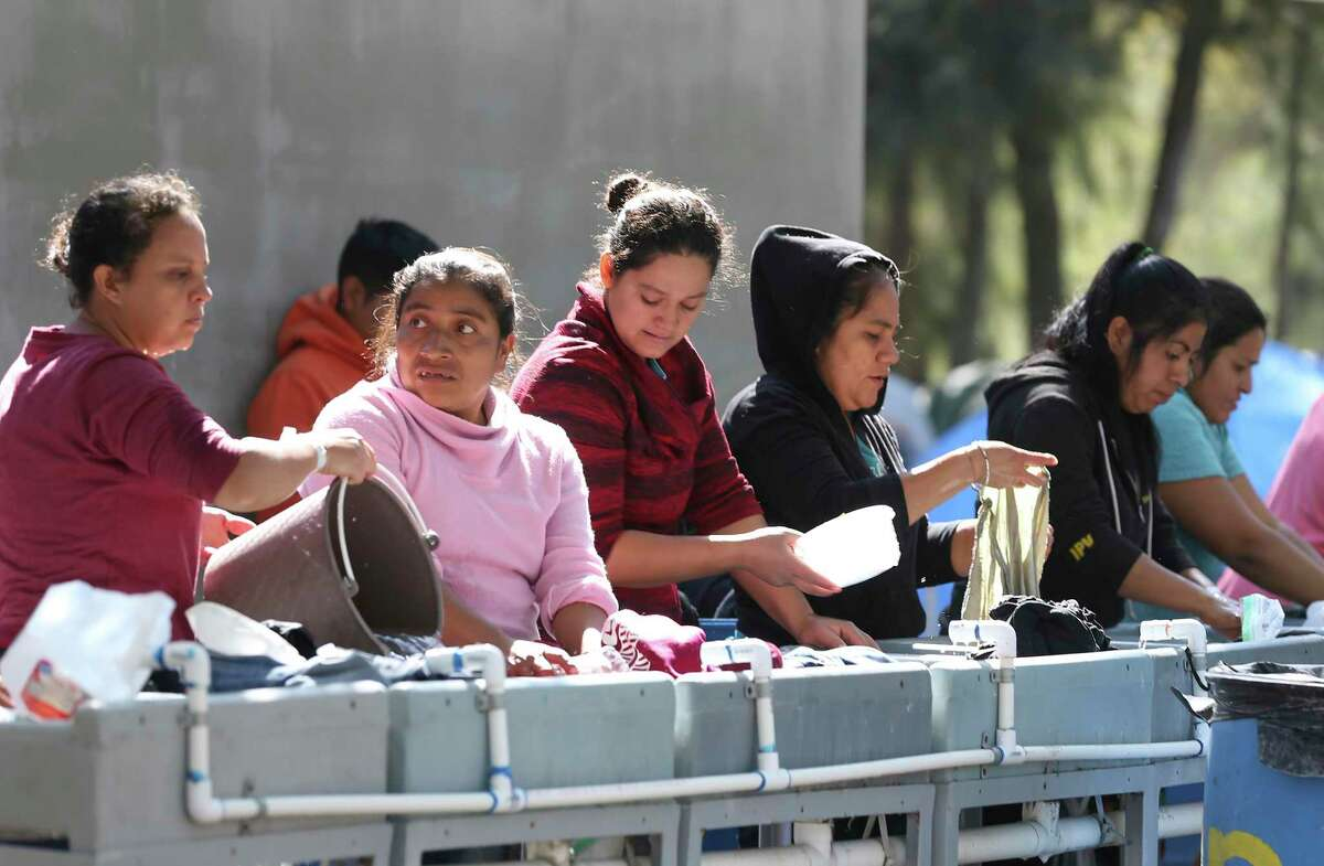 Women do their laundry at a station in a migrant camp in Matamoros, Mexico, Friday, Feb. 7, 2020. The camp formed last summer after the U.S. implemented the Migrant Protection Protocol, also known as Return to Mexico. Migrants were sent back to Mexico to await their immigration court date after crossing into the U.S. seeking asylum. The camp is home to around 2,200 mostly Central American migrants.