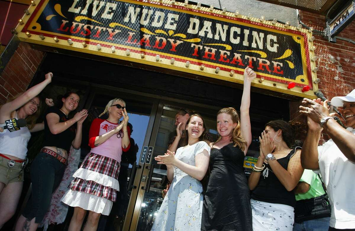FILE - Exotic dancers cheer after cutting a large garter belt to officially re-opening the Lusty Lady strip club June 26, 2003 in San Francisco. The dancers and support staff of the Lusty Lady made history by saving the famous strip club from going out of business by becoming the first employee-owned, fully unionized strip club in the nation.