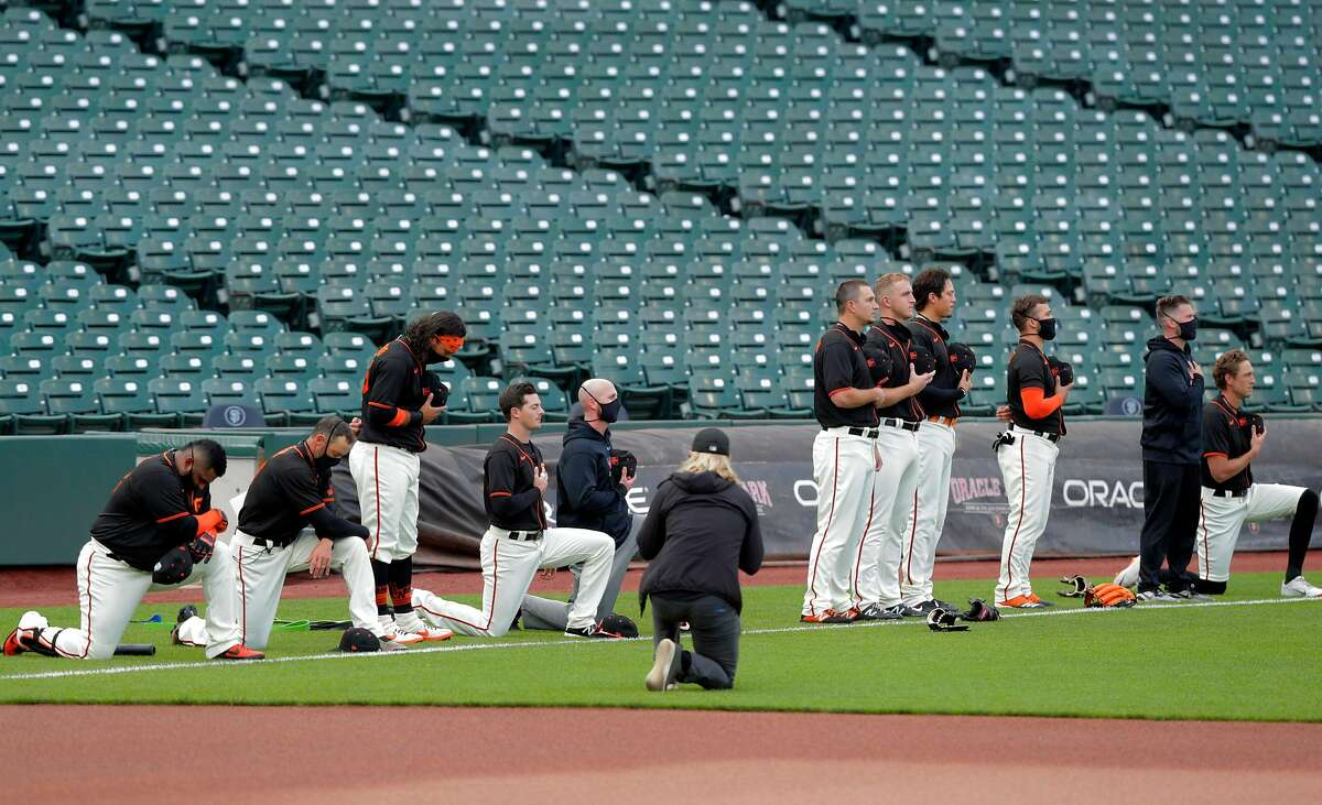 Several Giants players, and manager Gabe Kapler, second from left, took a knee during the national anthem before the San Francisco Giants played the Oakland Athletics in a summer exhibition game at Oracle Park in San Francisco, Calif., on Tuesday, July 21, 2020.