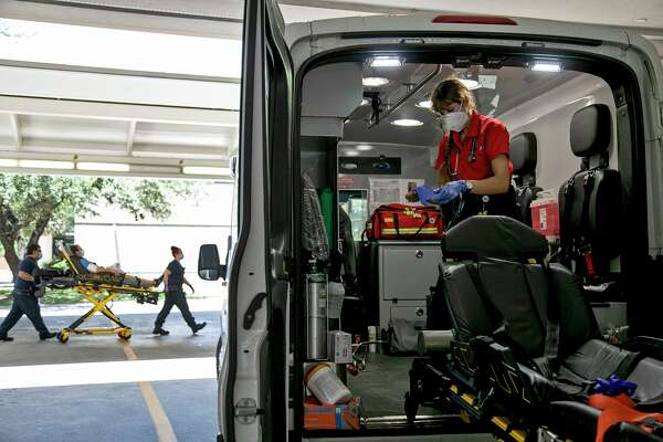 Paramedic Katheryn Wieding sterilizes the ambulance after transporting a patient, a process that is even more detailed amid the pandemic. Each surface — the medical cabinets, tubing, blood pressure cuff, stretcher — must be wiped down.