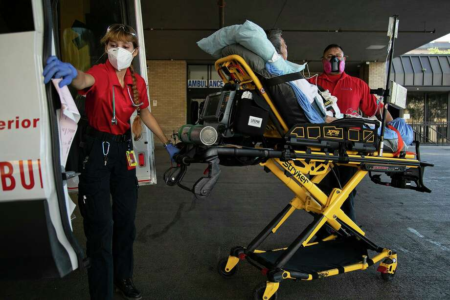 The temperature tops 100 degrees as paramedics Katheryn Wieding and George Lombardo lift a patient out of the ambulance and wheel him into the hospital. Photo: Lisa Krantz /Staff Photographer / San Antonio Express-News