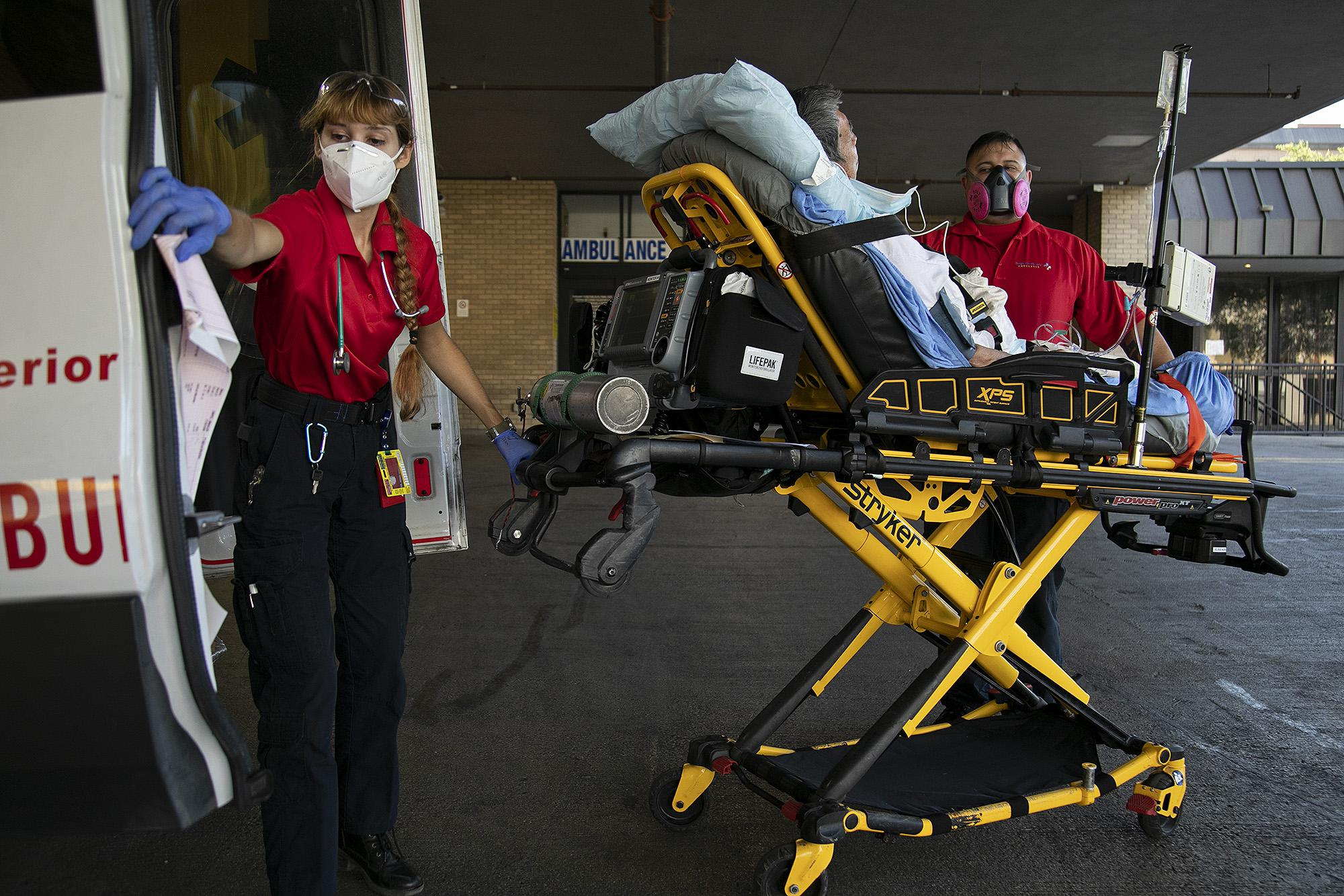 The temperature tops 100 degrees as paramedics Katheryn Wieding and George Lombardo lift a patient out of the ambulance and wheel him into the hospital.