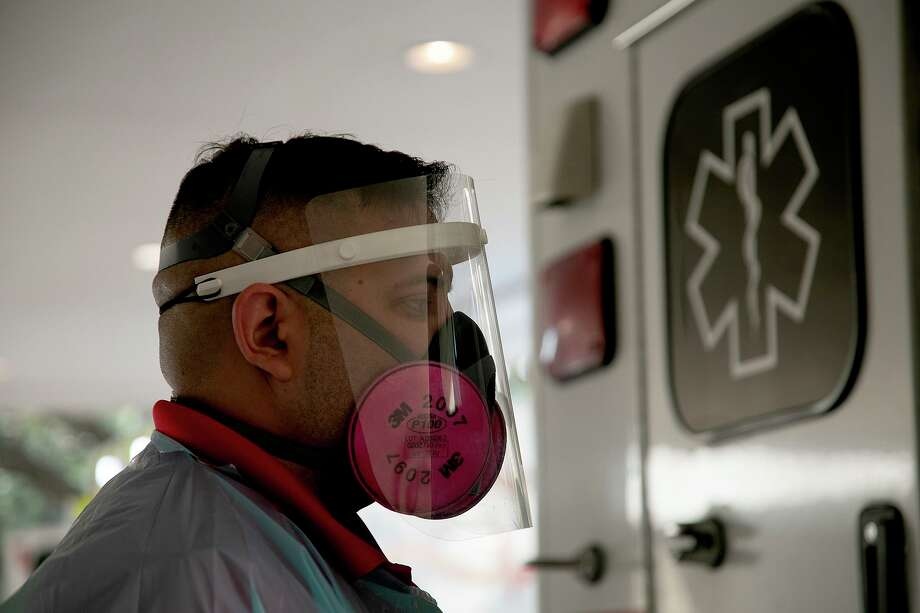 Before transporting patients with COVID-19, paramedics like Lombardo must don protective gear, including a respirator mask, face shield, gown and gloves. Photo: Lisa Krantz /Staff Photographer / San Antonio Express-News