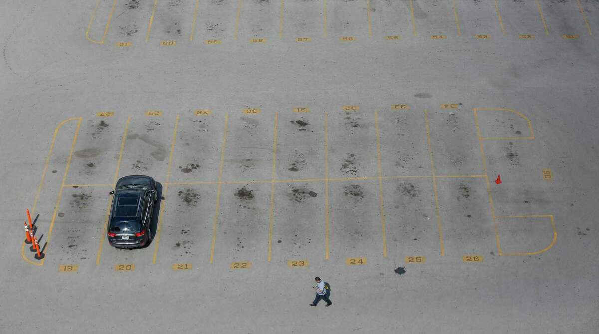 A man walks through an almost completely empty parking lot at Franklin and La Branch Streets in March.