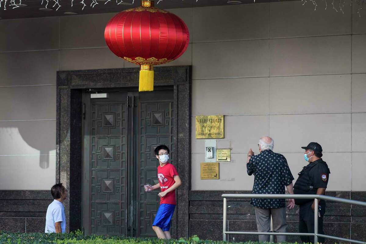 A security guard talks to a group of people outside the Consulate General of China Wednesday, July 22, 2020, in Houston.