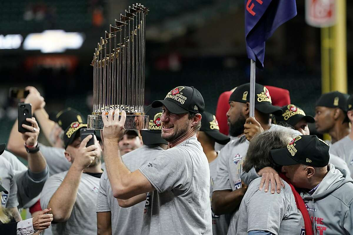 FILE - In this Oct. 30, 2019, file photo, Washington Nationals starting pitcher Max Scherzer celebrates with the trophy after Game 7 of baseball's World Series against the Houston Astros in Houston. Scherzer and the rest of the Nationals head into the 2020 season hoping to do something no major league club has done in quite some time: win back-to-back World Series. (AP Photo/David J. Phillip, File)