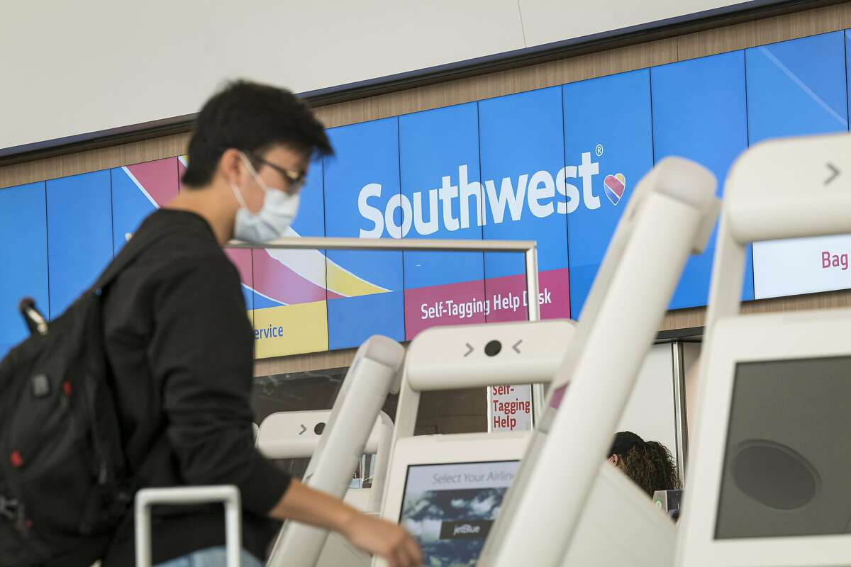 A traveler wearing a protective mask uses a kiosk at the Southwest Airlines Co. check-in counter at San Francisco International Airport (SFO) in San Francisco, California, U.S., on Wednesday, July 15, 2020. Southwest Airlines Co. is scheduled to release earnings figures on July 23. Photographer: David Paul Morris/Bloomberg