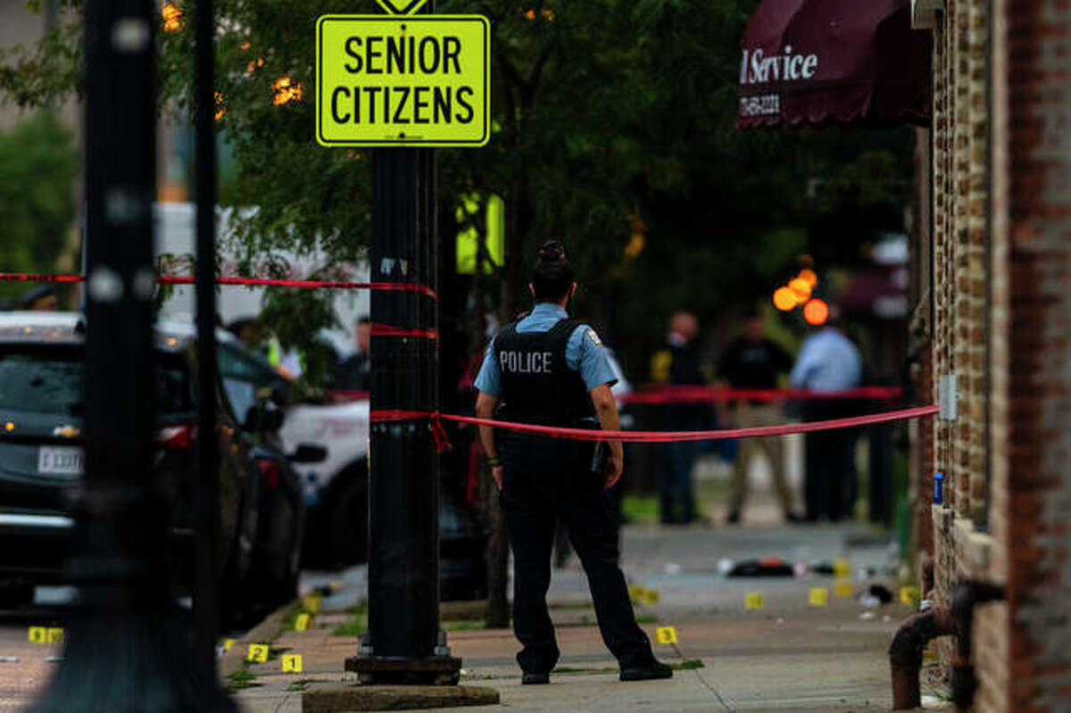 Chicago police investigate the scene of a mass shooting where more then a dozen people were shot in the Gresham neighborhood Tuesday.