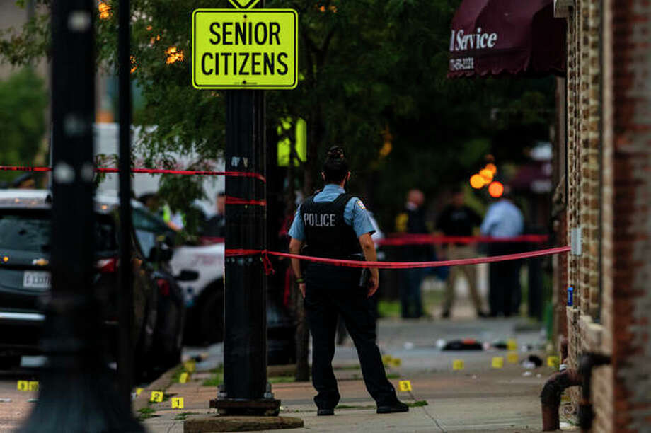 Chicago police investigate the scene of a mass shooting where more then a dozen people were shot in the Gresham neighborhood Tuesday. Photo: Tyler LaRiviere | Chicago Sun-Times (AP)