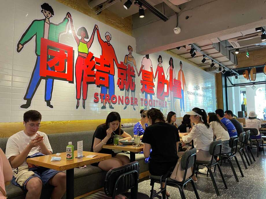 Cafes and restaurants in Beijing are operating almost as before. Many businesses require registration or health codes, but otherwise they operate normally. Photo: Washington Post Photo By Anna Fifield. / Anna Fifield