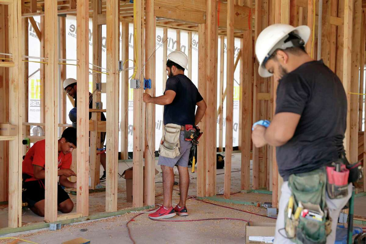 Contract electricians wire the inside of a house as home construction continues in the Freeman Ranch subdivision in Katy. Some 800 homes will eventually be built in the subdivision by The Woodlands homebuilder LGI Homes.
