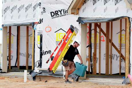 A contract worker moves ladders and tools between houses under construction as home building continues in the Freeman Ranch subdivision in Katy. Some 800 homes will eventually be built in the subdivsion by The Woolands homebuilder LGI Homes. LGI Homes vaulted into the Chronicle 100's top 10.