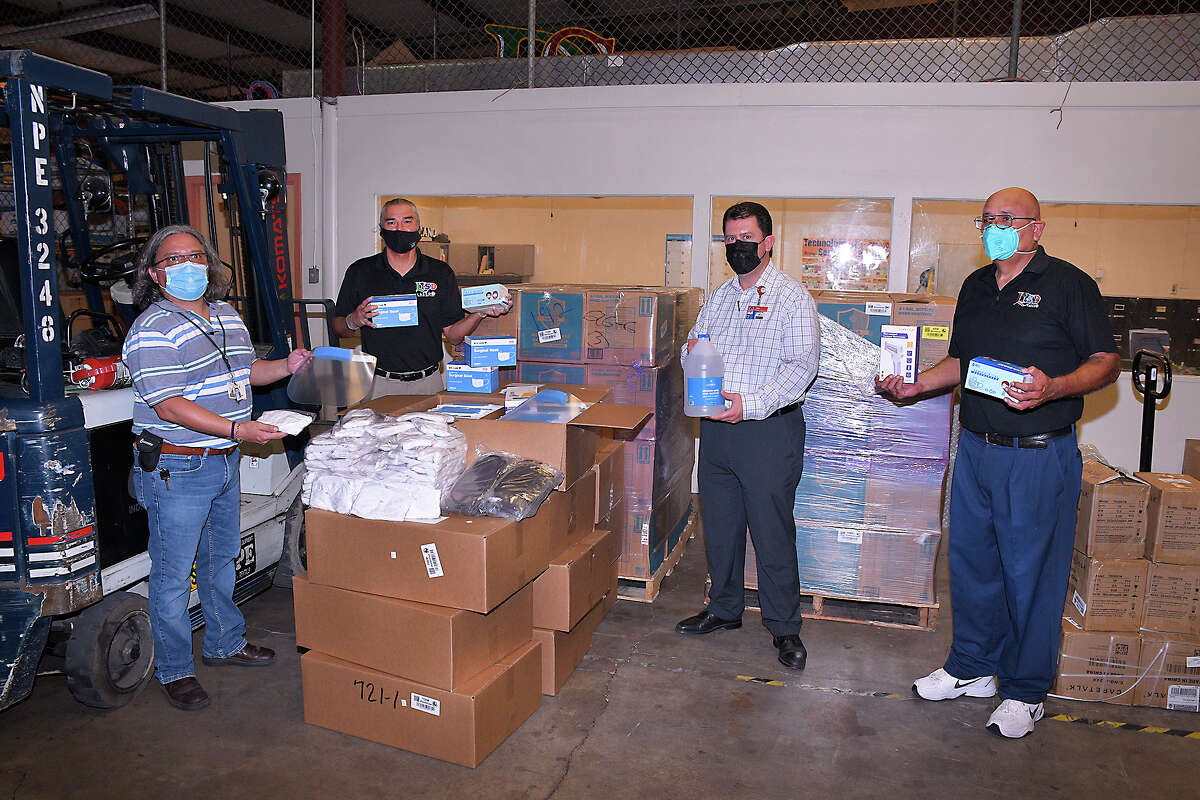 Assistant Superintendent for Accountability, Compliance and School Safety at LISD, Oscar Perez, second from left, JJ Gonzalez, right, Abel Elizondo and Sergio Neira from the Central Receiving Warehouse show some of the COVID-19 related personal protective gear provided by the state for LISD schools and departments, Wednesday, July 22, 2020 at the LISD Central Receiving Warehouse. The delivery included face coverings/mask for children and adults, hand sanitizing lotions and face shields.