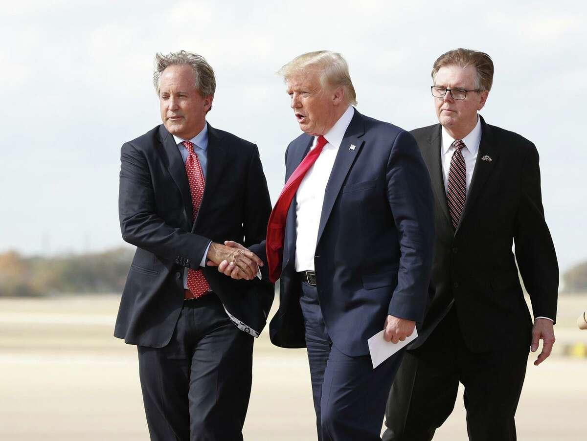 President Donald Trump greets Texas Attorney General Ken Paxton, left, as Lt. Gov. Dan Patrick follows at Austin Bergstrom International Airport on November 20, 2019. (Jay Janner/Austin American-Statesman/TNS)