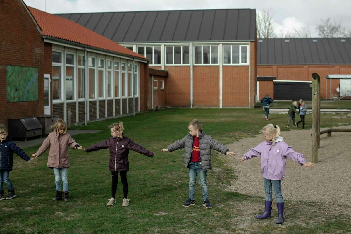 Children at a Logumkloster, Denmark elementary school, pictured in April, check their distancing before heading back into the building following recess. Denmark was one of the world's first coronavirus-hit countries to reopen schools in the spring, though its rate of confirmed cases and deaths at the time were far lower than Texas' current data.
